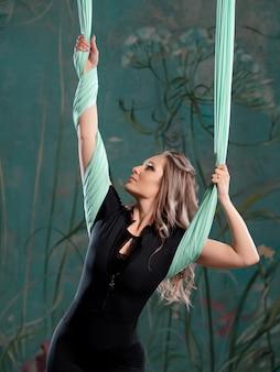 Porträt einer jungen sportlerin, die sich mit aero-yoga beschäftigt
