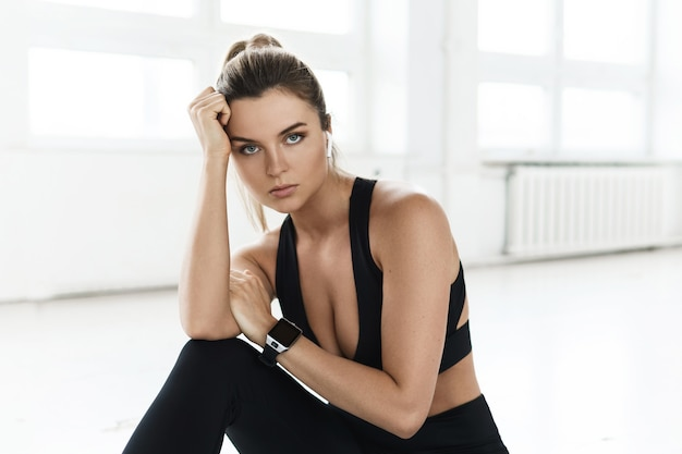 Porträt einer jungen sportlichen frau beim fitnesstraining im hellen fitnessstudio