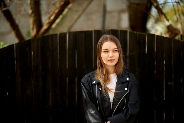 Porträt einer jungen stilvollen hipsterfrau, die vor einem zaun in einer schwarzen jacke steht.