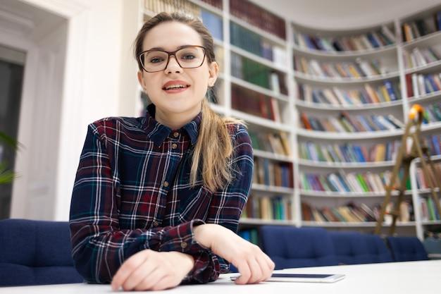 Porträt einer jungen studentin in gläsern, die in der öffentlichen bibliothek sitzt