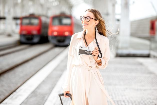 Porträt einer jungen touristin, die mit fotokamera im freien am bahnhof spazieren geht