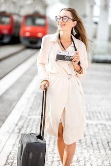Porträt einer jungen touristin, die mit koffer und fotokamera draußen am bahnhof spaziert