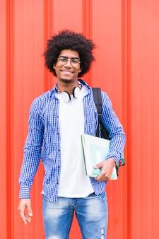 Porträt einer jungen tragetasche des männlichen studenten auf der schulter und büchern in der hand, die gegen rote wand stehen