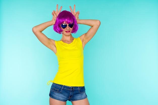 Porträt einer jungen transgender-frau mit problemhaut in rosa perücke und sonnenbrille in herzform auf blauem hintergrund