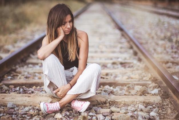 Porträt einer jungen traurigen frau, nachdenklich draußen auf der eisenbahnstrecke sitzend.