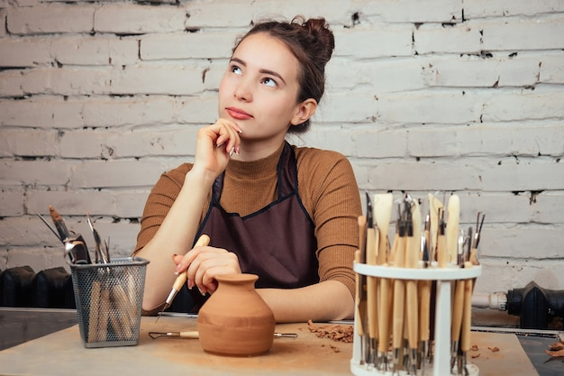Porträt einer jungen und fröhlichen frau, die eine vase aus ton hält. der töpfer arbeitet in einer töpferwerkstatt mit ton. das konzept der handwerkskunst und kreativität einer töpferei.