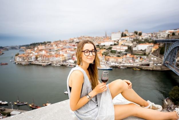 Porträt einer jungen und glücklichen frau, die porto-wein genießt und auf der terrasse mit schönem blick auf das stadtbild in porto, portugal sitzt