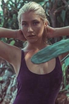 Porträt einer jungen und hübschen blonden frau, die in den tropischen büschen auf koh larn island in thailand in einem lila samtkleid mit ihren händen in ihrem blonden haar aufwirft.