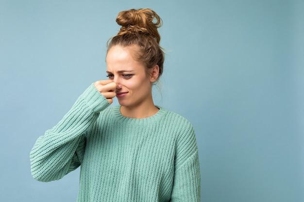Porträt einer jungen unzufriedenen schönen blonden frau mit aufrichtigen emotionen, die lässiges blau trägt