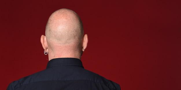 Porträt einer kahlen mannrückansicht auf rotem hintergrund