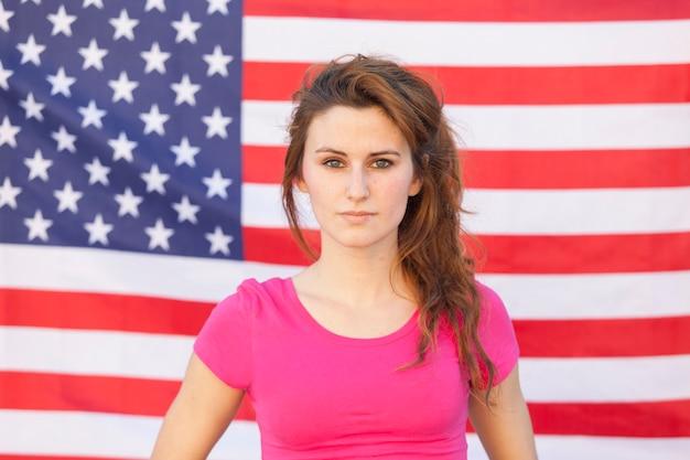 Porträt einer kaukasischen amerikanischen frau lokalisiert auf einer usa-flagge