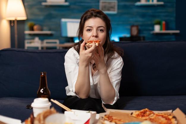 Porträt einer kaukasischen frau, die auf dem sofa sitzt und ein stück pizza isst und essen zum mitnehmen nach hause...