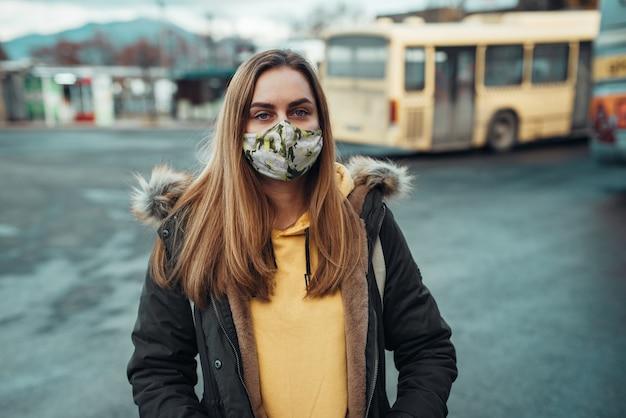 Porträt einer kaukasischen frau, die eine stilvolle maske mit blumendruck trägt