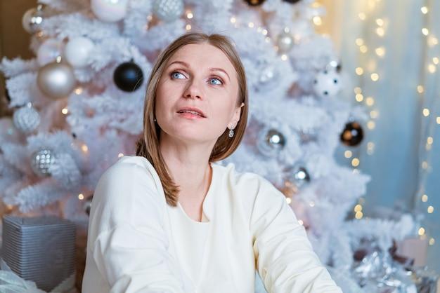 Porträt einer kaukasischen frau in einem leichten leichten pullover, der am weihnachtsbaum mit einem nachdenklichen blick fest sitzt