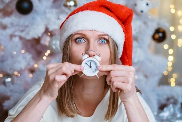 Porträt einer kaukasischen frau mit einem wecker in der hand und einer weihnachtsmütze vor dem hintergrund...