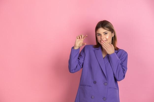 Porträt einer kaukasischen jungen frau auf rosa, emotional und ausdrucksstark