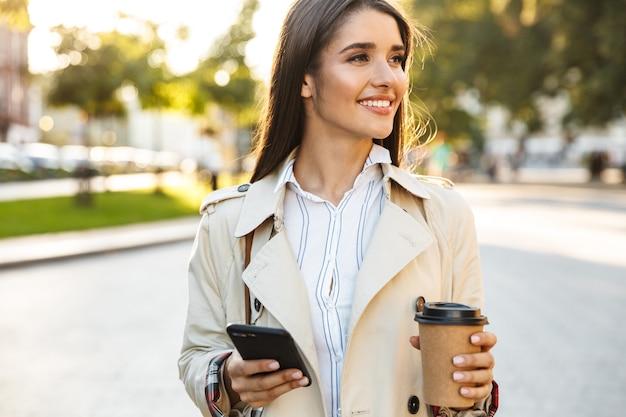 Porträt einer kaukasischen lächelnden frau mit mantel, die kaffee zum mitnehmen trinkt und beim gehen auf der stadtstraße auf dem handy tippt