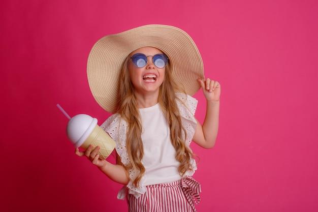 Porträt einer kleinen blondine mit sonnenbrille und hut mit einer dose kühlendem cocktail.