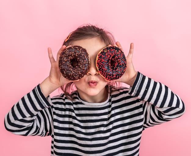 Porträt einer kleinen lächelnden mädchenbrünette mit und zwei appetitlichen donuts in ihren händen