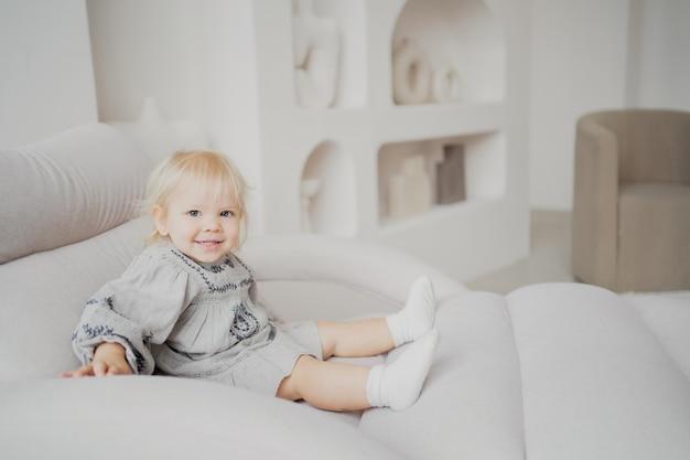Porträt einer kleinen tochter, eines blonden mädchens in einem stilvollen beigefarbenen kleid, das zu hause lustige spiele auf dem sofa spielt und lächelt. helles und stilvolles interieur der wohnung