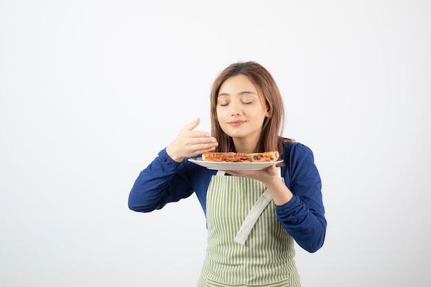 Porträt einer köchin in schürze riecht pizzastücke auf weiß