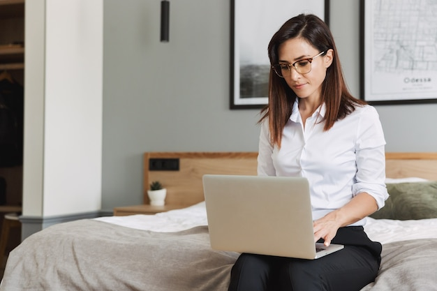 Porträt einer konzentrierten erwachsenen geschäftsfrau im formellen anzug, die auf dem laptop tippt, während sie auf dem bett in der wohnung sitzt