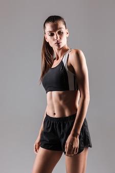 Porträt einer konzentrierten jungen fitnessfrau, die aufwirft