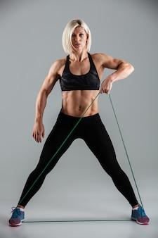 Porträt einer konzentrierten muskulösen erwachsenen sportlerin in voller länge