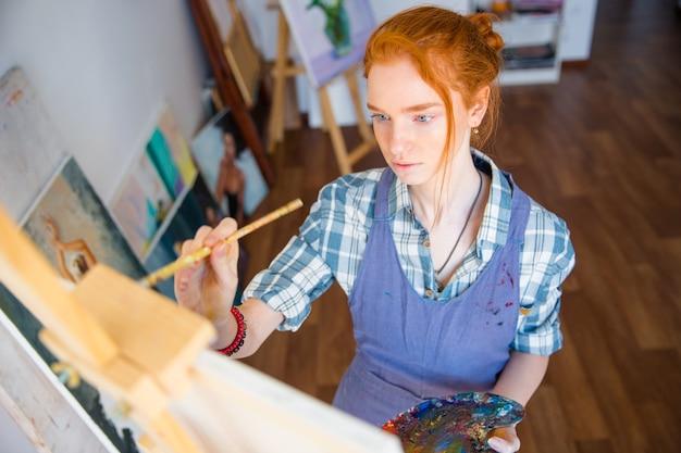 Porträt einer konzentrierten schönen jungen malerin mit kunstpalette und malerei auf leinwand mit pinsel in der künstlerwerkstatt