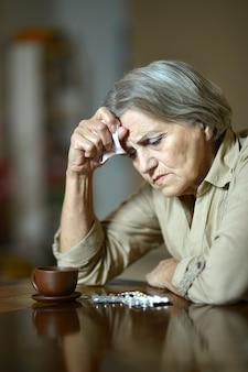 Porträt einer kranken älteren frau, die pillen nimmt
