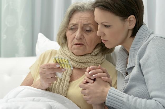 Porträt einer kranken älteren frau mit fürsorglicher tochter