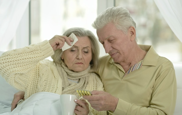 Porträt einer kranken älteren frau mit ihrem mann im bett