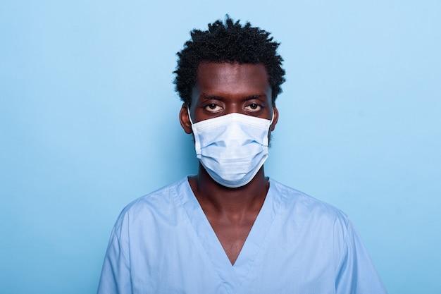 Porträt einer krankenschwester mit gesichtsmaske und uniform, die im studio steht