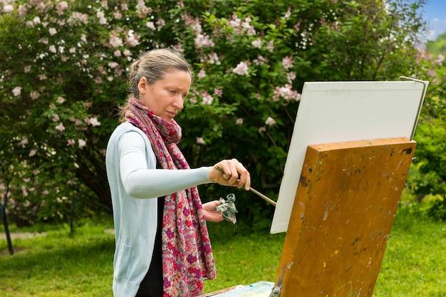 Porträt einer künstlerin mittleren alters, die gerade dabei ist, sein bild im freien mit dem hintergrund schöner bäume zu malen