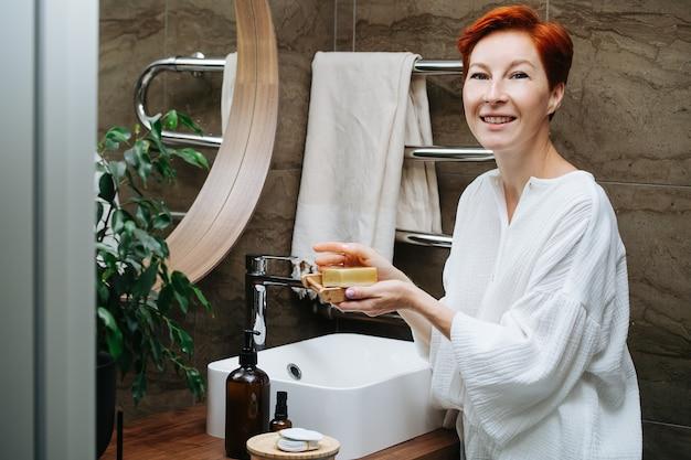 Porträt einer kurzhaarigen reifen frau, die ihre hände mit einem öko-seifenblock wäscht. sie steht in einem badezimmer vor dem spiegel.