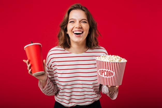 Porträt einer lachenden frau, die popcorn hält