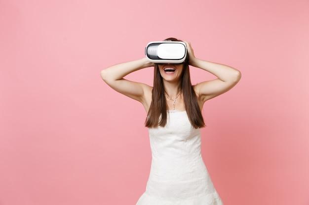 Porträt einer lachenden frau im weißen kleid, headset der virtuellen realität, das sich am kopf festklammert