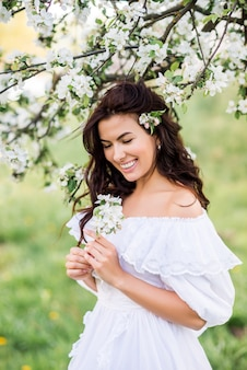 Porträt einer lachenden frau in einem blühenden garten. ein mädchen lächelt im frühlingsgarten.