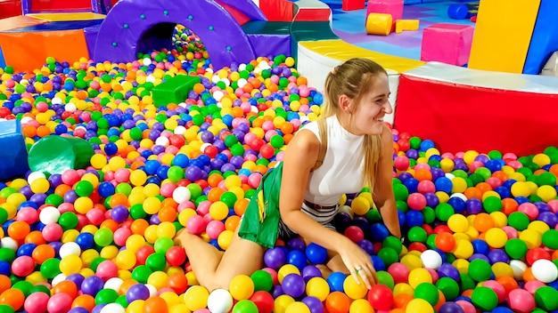 Porträt einer lachenden jungen frau, die mit vielen bunten plastikbällen auf dem kinderspielplatz im einkaufszentrum in den pool fällt?
