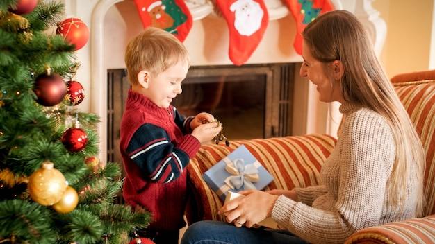 Porträt einer lachenden jungen mutter mit einem kleinen jungen, der am weihnachtsmorgen im wohnzimmer geschenke und geschenke auspackt