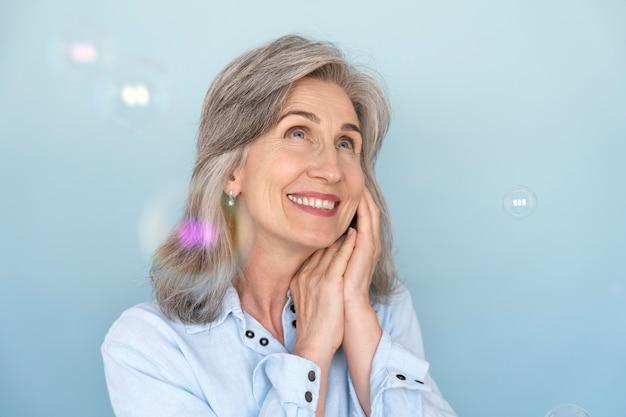 Porträt einer lächelnden älteren frau, die beim spielen mit blasen posiert
