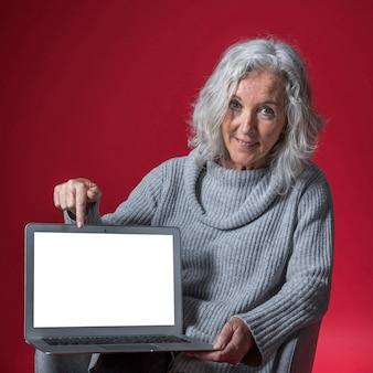 Porträt einer lächelnden älteren frau, die ihren finger auf laptop gegen roten hintergrund zeigt