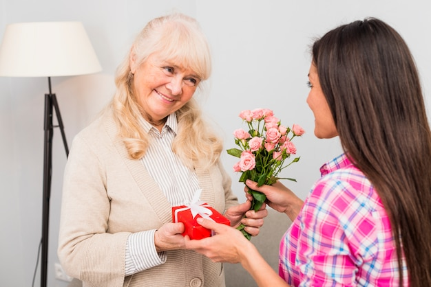 Porträt einer lächelnden älteren frau, die ihrer jungen tochter geschenk und rosen gibt