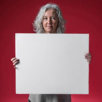 Porträt einer lächelnden älteren frau, die weißes leeres plakat gegen roten hintergrund zeigt
