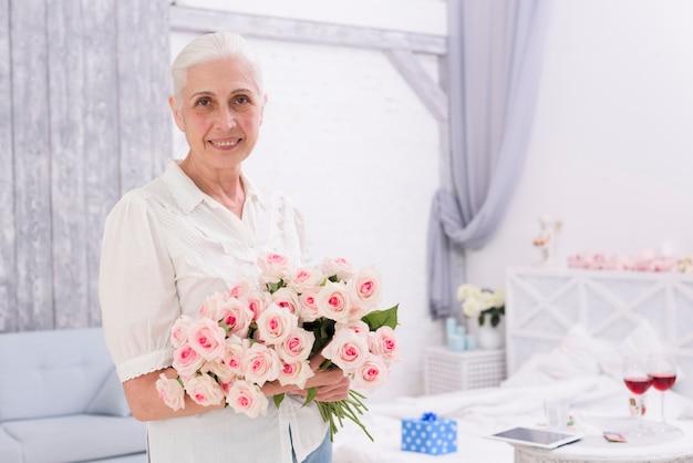 Porträt einer lächelnden älteren frau, die zu hause blumenstrauß von rosenblumen hält