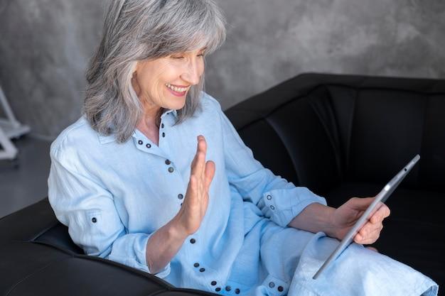 Porträt einer lächelnden älteren frau, die zu hause ein tablet für einen videoanruf verwendet und winkt