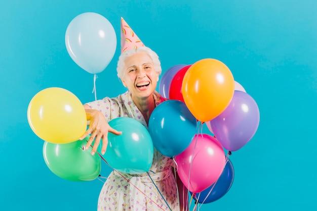Porträt einer lächelnden älteren frau mit bunten ballonen auf blauem hintergrund