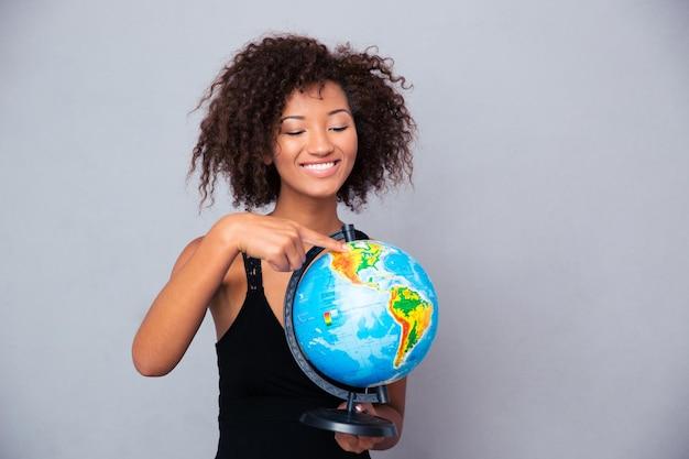 Porträt einer lächelnden afroamerikanischen frau, die globus über graue wand hält
