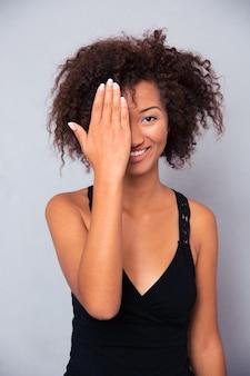 Porträt einer lächelnden afroamerikanischen frau, die ihr auge bedeckt und vorne über graue wand schaut
