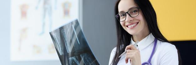 Porträt einer lächelnden arztfrau, die ein röntgenbild-konzept für medizinische dienste hält